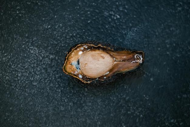 Metà dell'avocado viziato marcio malsano su sfondo scuro. avocado cattivo tagliato a metà. avocado ammuffito