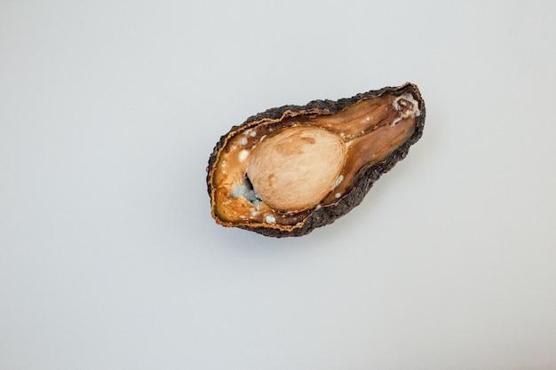 La metà dell'avocado viziato marcio malsano su sfondo chiaro. avocado cattivo tagliato a metà. avocado ammuffito