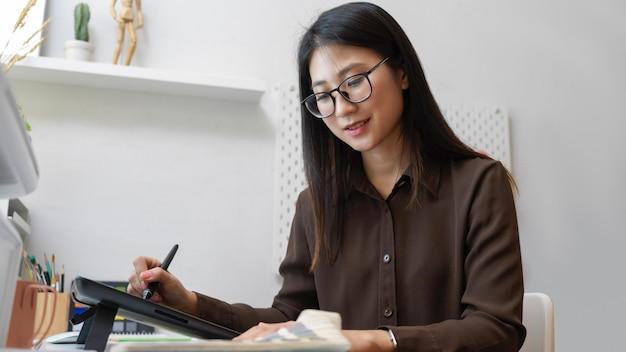 Ritratto di mezza lunghezza del grafico femminile che sorride mentre lavora con la tavoletta grafica e il campione di colore