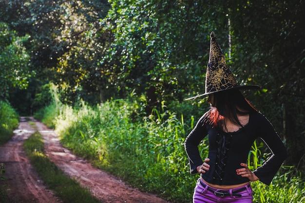 Progettazione di arte di halloween, bella giovane donna in cappello delle streghe nella foresta