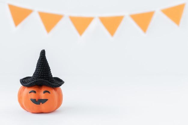 Sfondo di halloween di zucca con cappello nero con faccia buffa su una superficie grigia per le vacanze