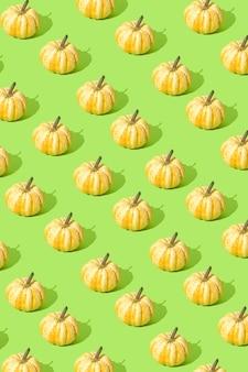 Sfondo di halloween zucche disposte in uno schema su un bacground verde autunno ottobre concept
