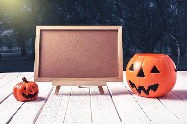 Sfondo di halloween zucca spettrale, lavagna sul pavimento di legno e foresta scura. hallowee