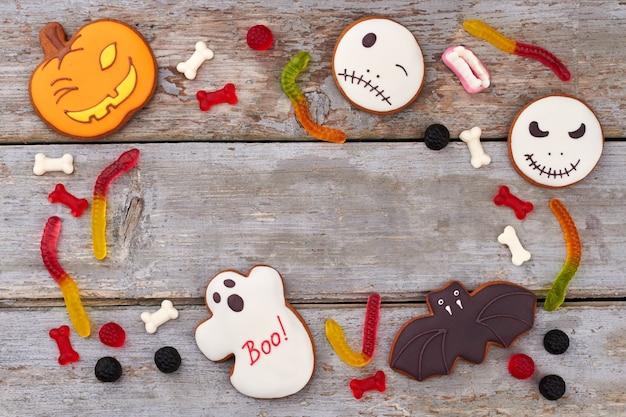 Sfondo di halloween con cornice di caramelle gommose da biscotti di halloween e caramelle di gelatina con spazio di copia...