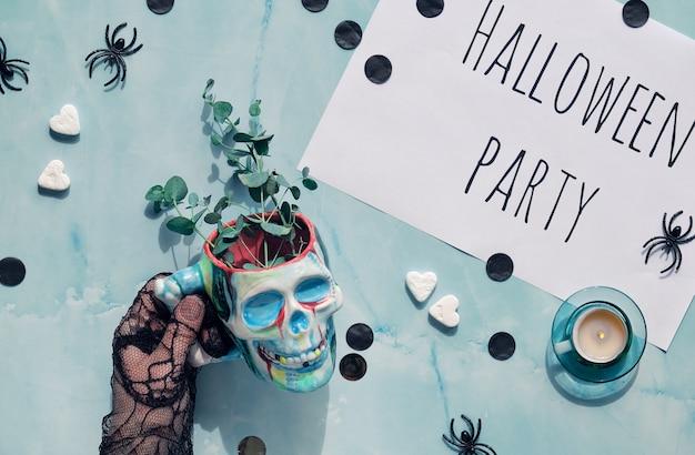 Sfondo di halloween con la mano che tiene la tazza del cranio con ramoscelli di eucalipto. lay piatto con decorazioni per feste.