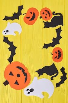 Sfondo di halloween con decorazioni di carta sagome di carta di halloween con copia spazio vuoto su giallo...