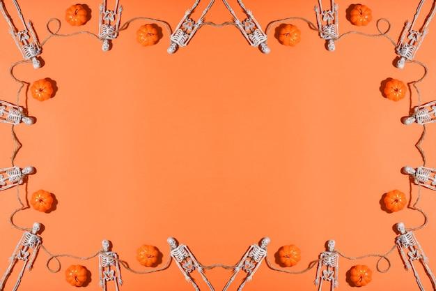 Sfondo di halloween con scheletri e zucche che formano una cornice.