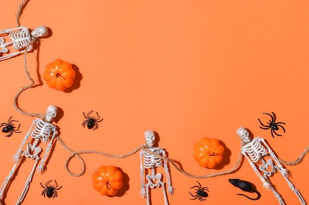 Sfondo di halloween con scheletri e zucche e ragni che formano una cornice. layout piatto, vista dall'alto, posto da copiare.