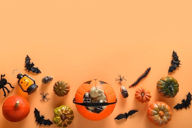 Banner di halloween di divertenti decorazioni per feste, ciotola di caramelle, zucche, dolci, pipistrelli, teschi, ragno spettrale su sfondo arancione.