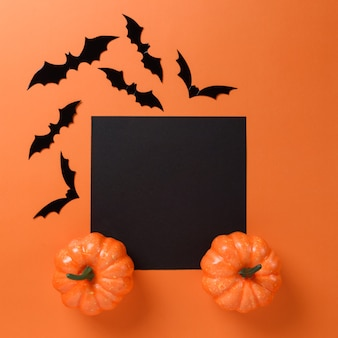 Decorazioni di pipistrello di halloween su uno sfondo arancione