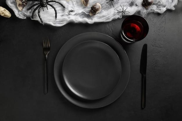 Regolazione della tavola nera di halloween con ragno, teschio e web sul tavolo scuro nero