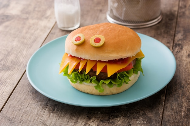 Mostro di hamburger di halloween sulla tavola di legno
