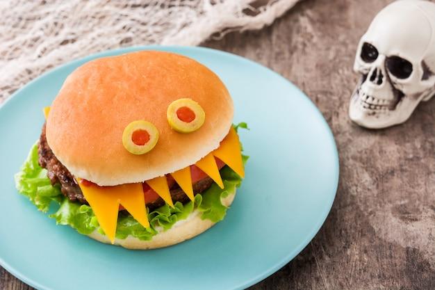 Mostri dell'hamburger di halloween sulla tavola di legno