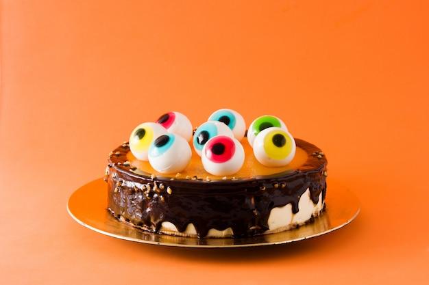 Torta di halloween con decorazione di occhi di caramelle su sfondo arancione