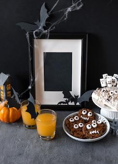 Candy bar di halloween: mostri divertenti fatti di biscotti con cioccolato e vermi gommosi, fantasmi marshmelow vicino sul tavolo