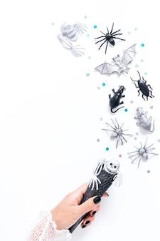 Carta di halloween su bianco con decorazioni natalizie nere e argento. donna con manicure nera che tiene cono nero con pipistrelli e fantasmi che volano intorno, copia spazio, vacanza gotica piatta, immagine verticale