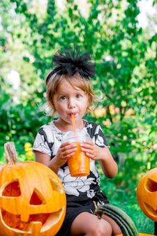 Halloween, bambino vestito di nero che beve cocktail di zucca, dolcetto o scherzetto, bambina vicino alla decorazione jack-o-lantern nel legno, all'aperto.