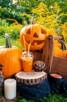 Cocktail di halloween con decorazione di zucche sullo sfondo. un pugno per una festa