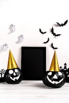 Composizione di halloween. cornice nera e arte di carta villaggio abbandonato, zucca su bianco.