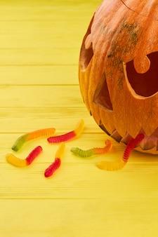 Composizione di halloween su sfondo colorato zucca di halloween che vomita con vermi di gelatina buon halloween...