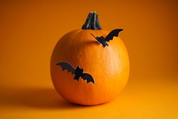 Concetto di halloween. zucca di halloween e pipistrelli su uno sfondo arancione.