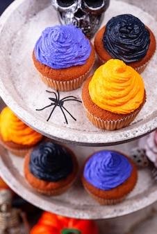 Cupcakes di halloween con crema e decorazioni nere, viola e arancioni