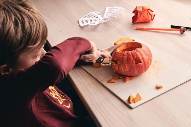 Idee per halloween, decorazioni e vacanze: primo piano di un bambino con zucca intagliata a coltello o jack-o-lantern. il ragazzo di 6 anni ha un'attività divertente in famiglia. la mamma trascorre del tempo con il figlio insieme