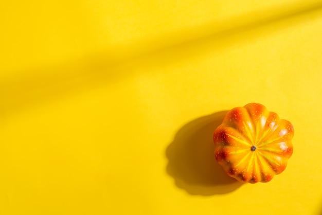 Zucca colorata arancione matura della decorazione di halloween su un colore giallo