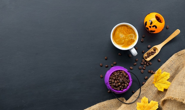 Decorazione di halloween con caffè caldo e fagioli su sfondo scuro. laici piatta. copia spazio per il testo.