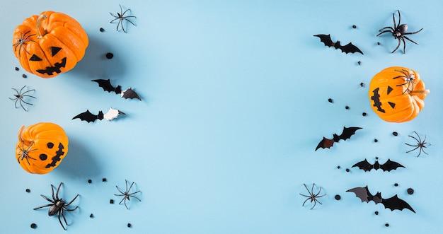 Decorazioni di halloween a base di zucca, pipistrelli di carta e ragno nero su sfondo blu pastello. vista piana laico e superiore con copia spazio per il testo.