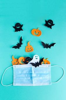 Decorazioni di halloween zucche, pipistrelli e fantasmi e maschera medica su sfondo turchese