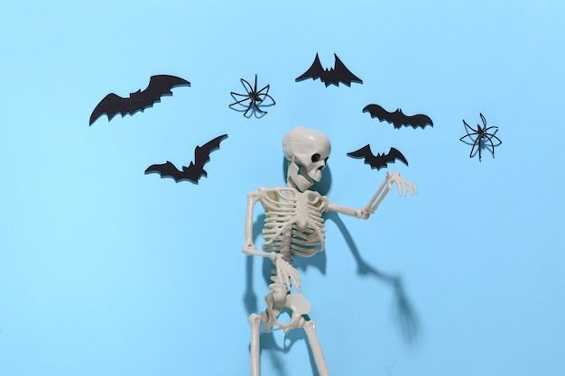 Halloween, decorazioni e concetto spaventoso. scheletro e ragni, pipistrelli neri sorvolano il blu luminoso