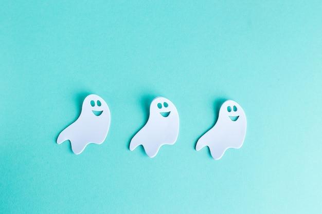Decorazioni di halloween fantasmi bianchi su sfondo turchese
