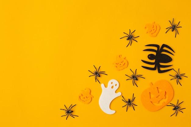 Decorazioni di halloween con ragni neri, zucche pazze e fantasma su sfondo arancione. appartamento laico, vista dall'alto, copia dello spazio.
