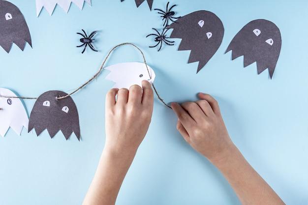 Halloween fai da te e creatività per bambini. istruzioni dettagliate per creare ghirlande di fantasmi dalla carta
