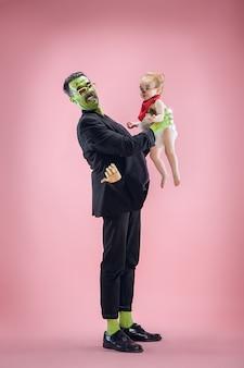Famiglia di halloween. felice padre e bambini ragazza appena nata in costume di halloween e trucco. tema sanguinante: il pazzo maniaco su sfondo rosa dello studio