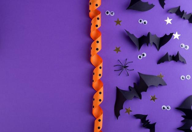 Modello di cornice di halloween con pipistrelli di carta nera e occhi spettrali di plastica su uno sfondo viola colorato.