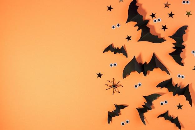 Modello di cornice di halloween con pipistrelli di carta nera e occhi spettrali di plastica su uno sfondo giallo colorato.