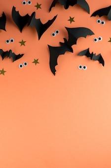 Modello di cornice di halloween con pipistrelli di carta nera e occhi spettrali di plastica su uno sfondo di colore giallo.