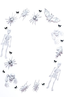 Cornice di halloween con pipistrelli d'argento dipinti, scheletri, ragni e coriandoli di gatto nero su sfondo bianco, spazio copia, immagine verticale, vista dall'alto
