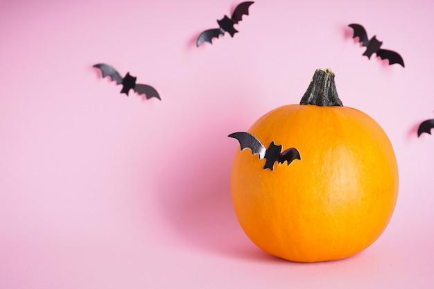 Zucca e pipistrelli freschi di halloween su uno sfondo rosa. spazio per il testo.