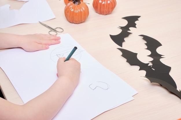 Decorazioni fatte a mano per halloween. il bambino realizza decorazioni di halloween con la carta, la ragazza disegna zucche e fantasmi su carta bianca