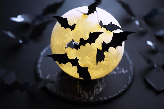 Concetto di vacanza di halloween. vecchio tavolo in pietra a forma di pipistrelli. decorazioni di carta di halloween su sfondo scuro. giocattolo della luna.