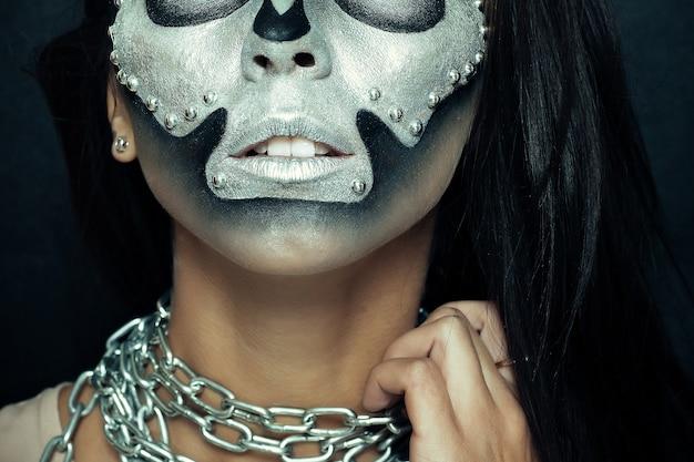 Halloween, vacanze, stile di vita, persone, bellezza, concetto creativo- halloween e tema trucco creativo: modello di bella ragazza con corpo nero con vernice teschio maschera d'argento su sfondo scuro in studio