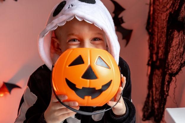 Ragazzo di halloween per bambini con secchi di caramelle di zucca in costume da scheletro a casa pronto per dolcetto o scherzetto