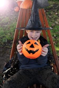 Bambini di halloween. simpatico ragazzino, bambino che indossa un cappello da strega con un secchio di caramelle arancioni jack o lantern. felice halloween.