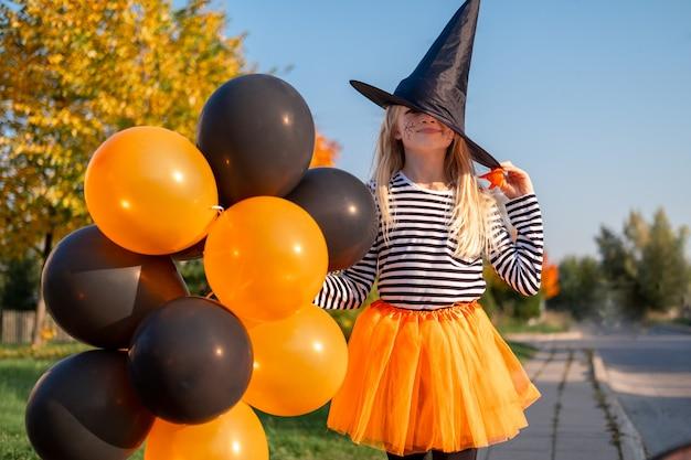 Bambini di halloween. ragazza sorridente del ritratto in cappello della strega con palloncini arancioni e neri. bambini divertenti in