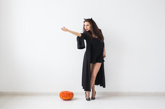 Halloween e concetto di masquerade - bella giovane donna in posa con zucca jack-o'-lantern su sfondo chiaro con spazio di copia