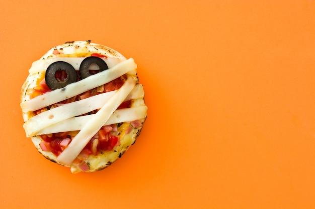 Mini pizze delle mummie di halloween su fondo arancio