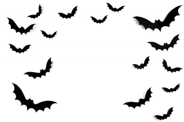 Arte di carta di halloween. pipistrelli di carta neri volanti su bianco